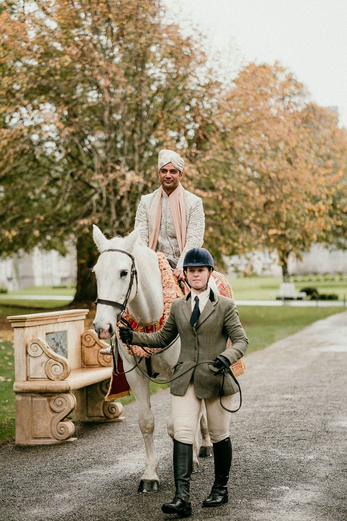 Indian groom, Miten making his entry to his Indian fusion wedding, on a horse at Ashford Castle in County Mayo, Ireland.