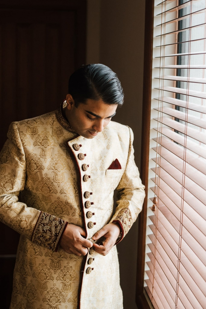 Indian groom, Rohit getting ready in his sherwani suit on his wedding day.