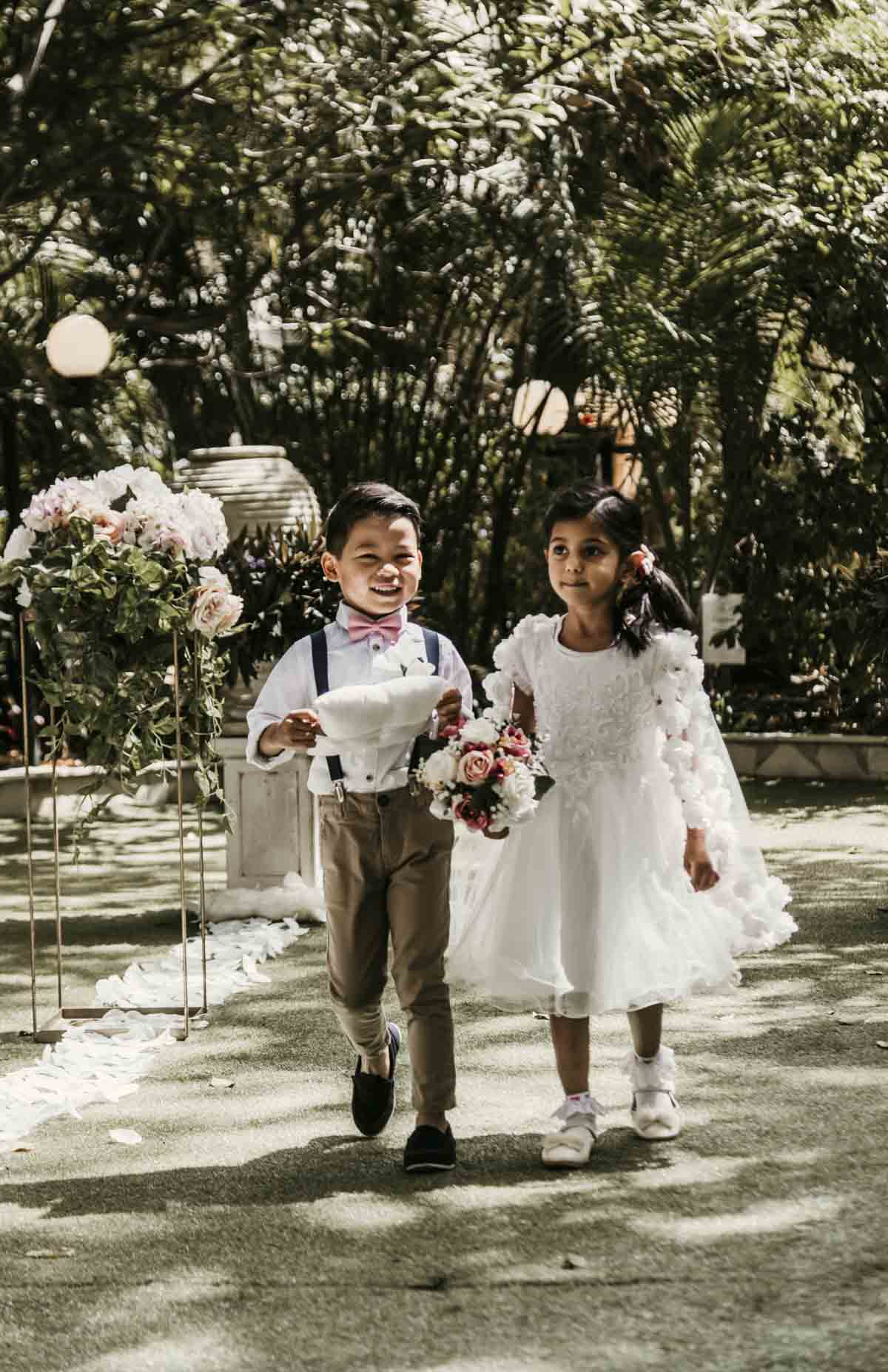 Shay and Uppi's modern and romantic garden civil wedding ceremony took place at Boulevard Gardens in Brisbane, Australia. They had a flower girl and ring boy for their outdoor wedding.