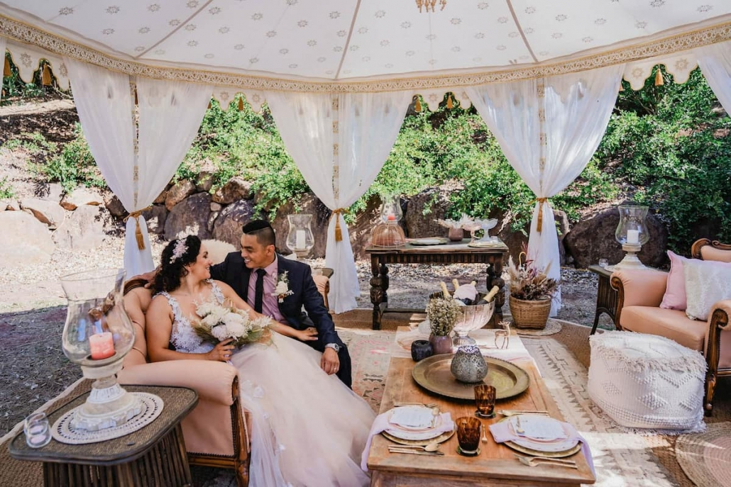 Couple sitting in luxury outdoor tent by luxury tent hire and event specialists in Queensland, Glamacamp Weddings and Events.