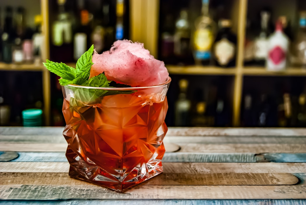Fancy Negroni cocktail served with cotton candy and mint garnish