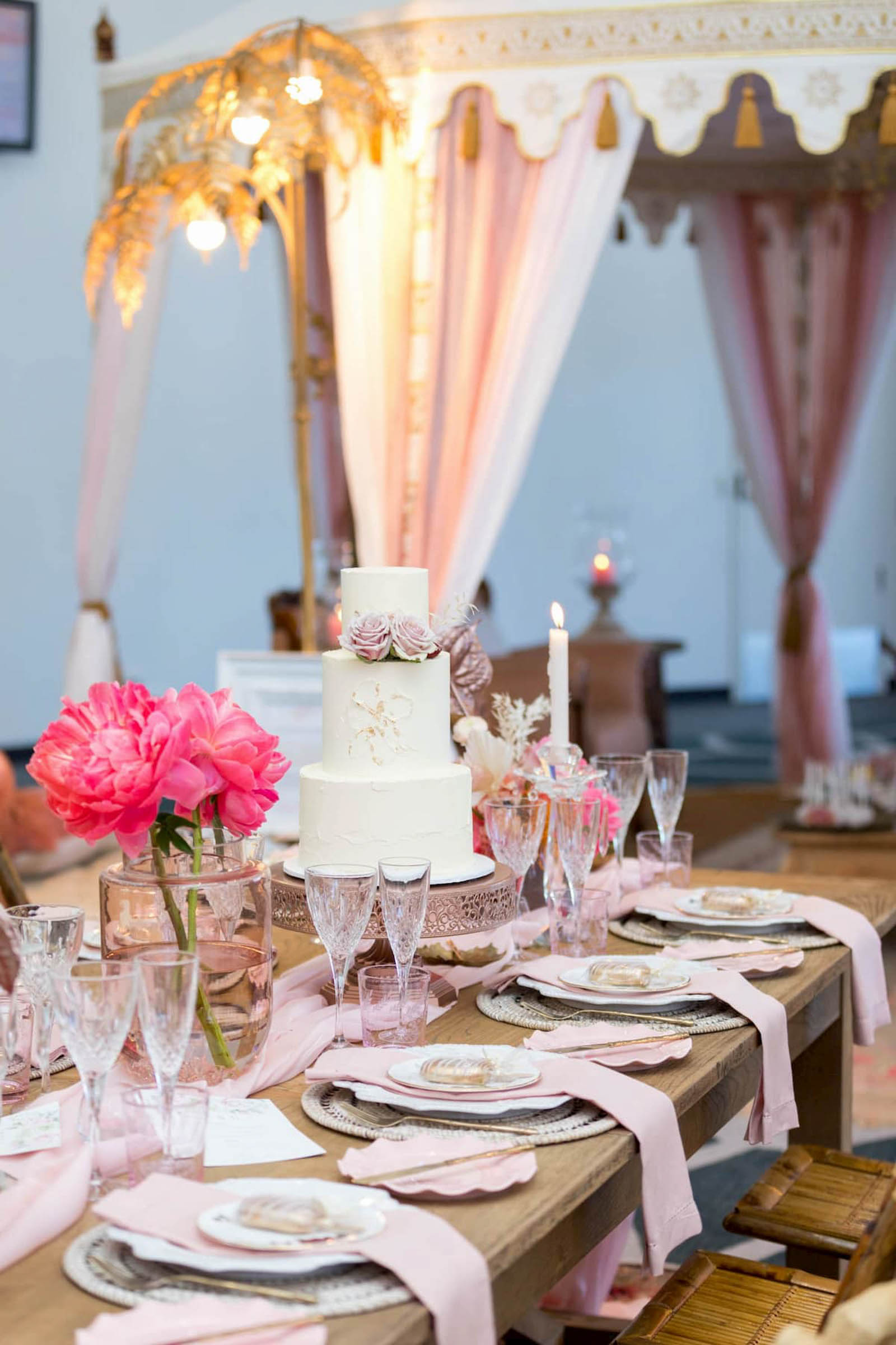 Luxury outdoor picnic setting with 3 tier wedding cake and pink and gold place settings